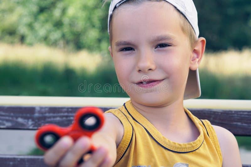 Junger kaukasischer Schüler, der populäres Unruhespinnerspielzeug - nahes hohes Porträt hält Glückliches lächelndes Kind, das mit stockfoto