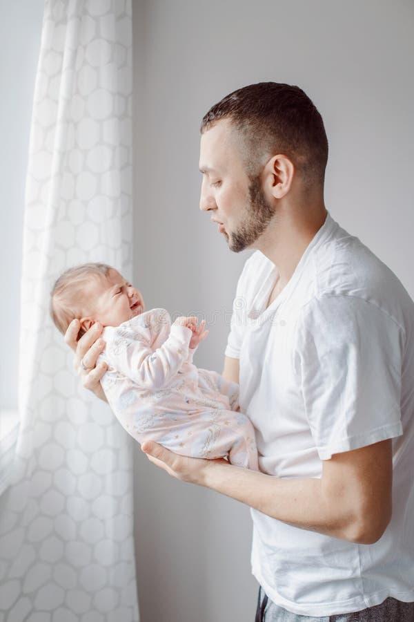 Junger kaukasischer Vater, der versucht, sich neugeborenes Baby zu beruhigen M?nnliches Mannelternteil, das Schwingkind auf seine lizenzfreies stockfoto