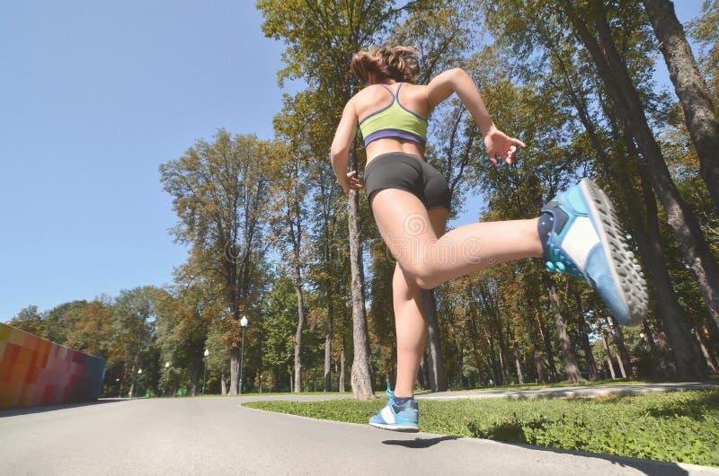 Junger kaukasischer weiblicher Athlet in einem hellgrünen Sport-BH und in den Sportkurzen hosen läuft in einen Sommerpark im Frei lizenzfreies stockfoto