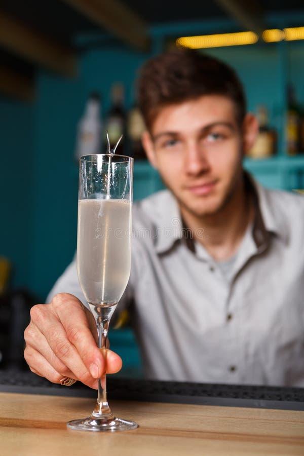 Junger Kellner bietet Alkoholcocktail in der Nachtclubbar an lizenzfreies stockfoto