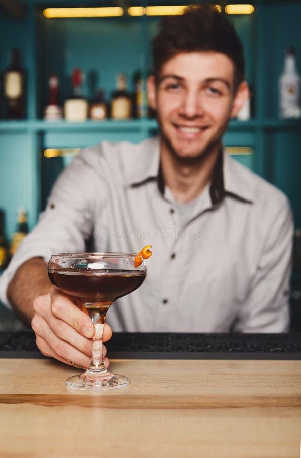 Junger Kellner bietet Alkoholcocktail in der Nachtclubbar an lizenzfreies stockbild