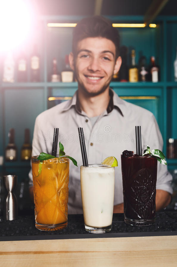 Junger Kellner bietet Alkoholcocktails in der Nachtclubbar an stockbilder