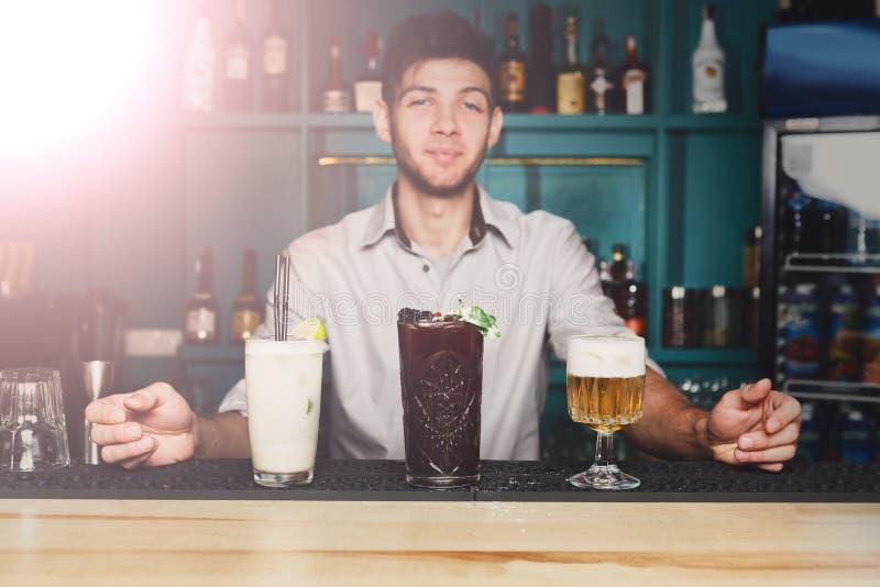 Junger Kellner bietet Cocktails in der Nachtclubbar an stockbilder