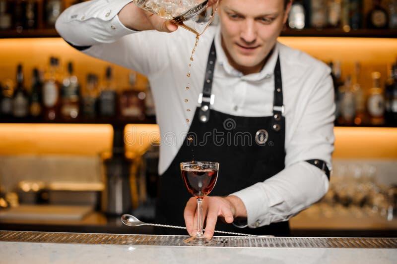 Junger Kellner, der alkoholisches Getränk in ein elegantes Glas gießt lizenzfreie stockfotos