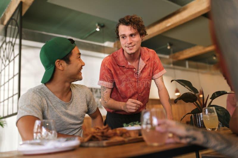 Junger Kellner, der mit einer Gruppe lächelnden Bistrokunden spricht lizenzfreies stockbild