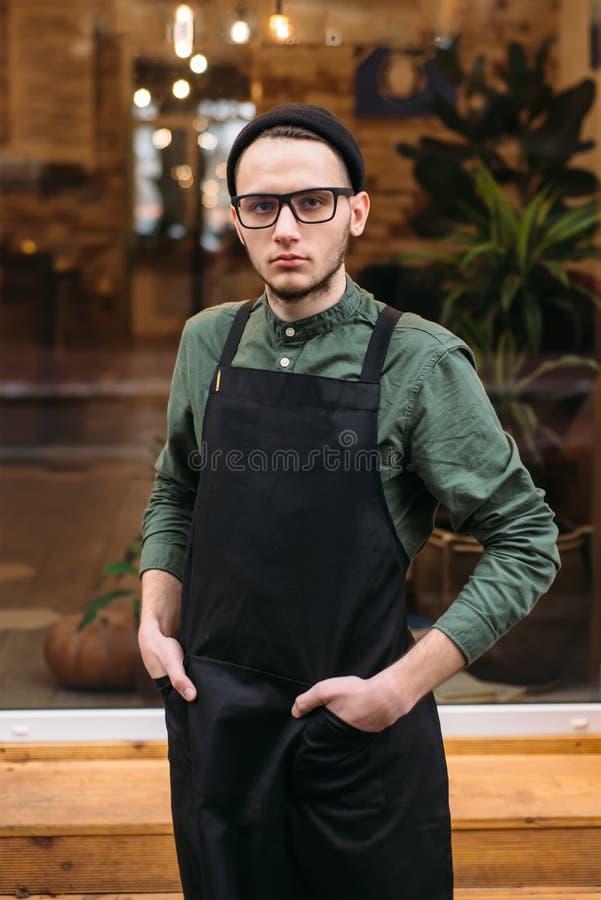 Junger Kellner im schwarzen Schutzblech lizenzfreies stockbild