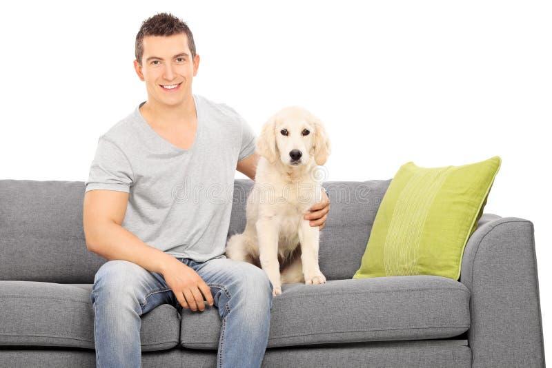 Junger Kerl, der auf einem Sofa mit einem netten Welpen sitzt stockbilder