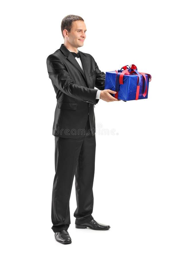 Junger Kerl, der ein eingewickeltes Geschenk hält stockfotos