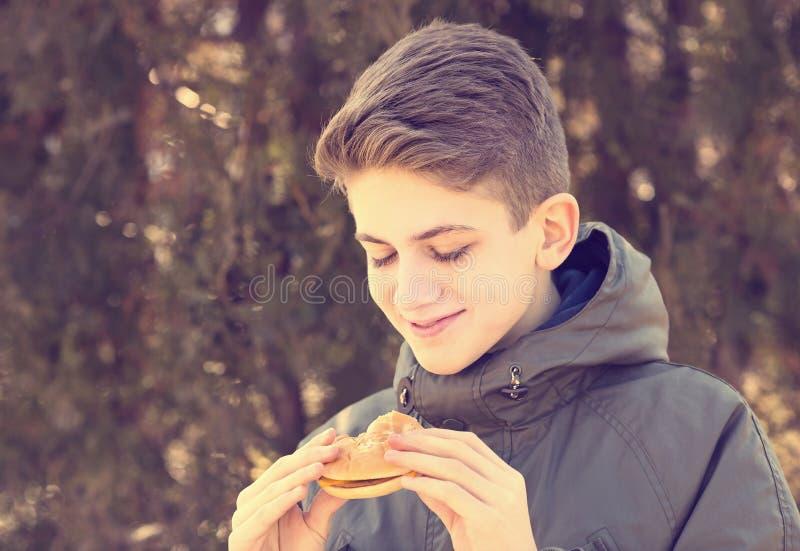 Junger Kerl, der einen Cheeseburger isst lizenzfreie stockfotos