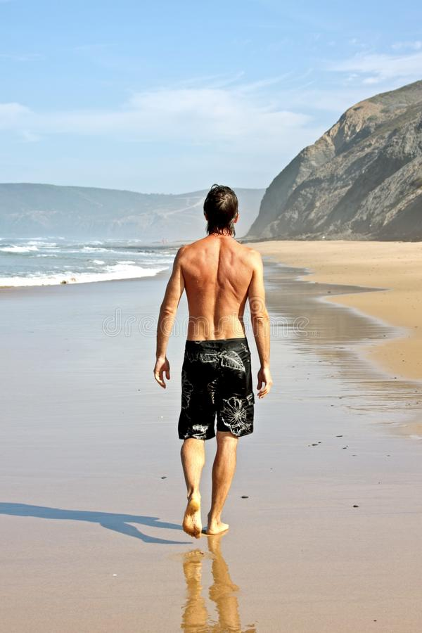 Junger Kerl, der einen Weg entlang dem Strand hat stockfotografie