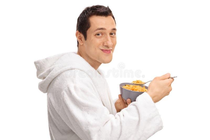 Junger Kerl, der Getreide von einer Schüssel isst lizenzfreie stockfotografie