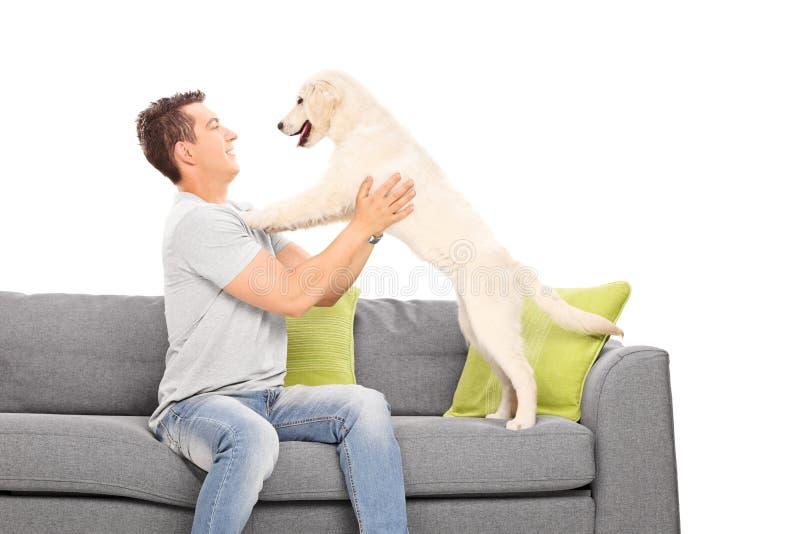 Junger Kerl, der mit seinem Hund spielt lizenzfreies stockfoto