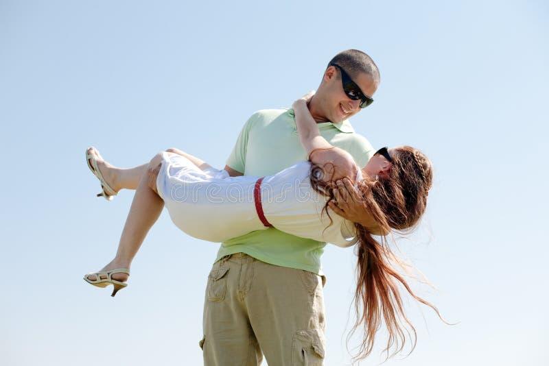 Junger Kerl, der seine Freundin in seinen Armen trägt stockfotos