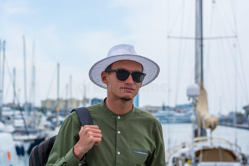 Junger Kerl in einem Hut und in der Sonnenbrille steht im Hafen von Barce lizenzfreie stockfotos