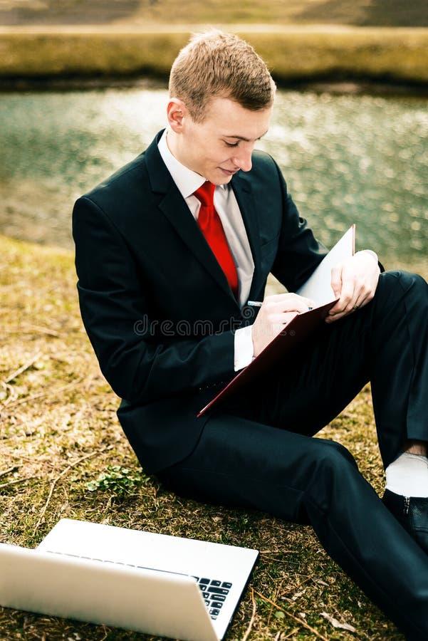 Junger Kerl in einem schwarzen Anzug und in einer roten Bindung schreibt in ein Notizbuch ein Mann arbeitet entfernt in der Natur stockbilder