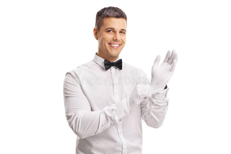 Junger Kerl in einem Smoking, das auf Handschuhe sich setzt stockbilder