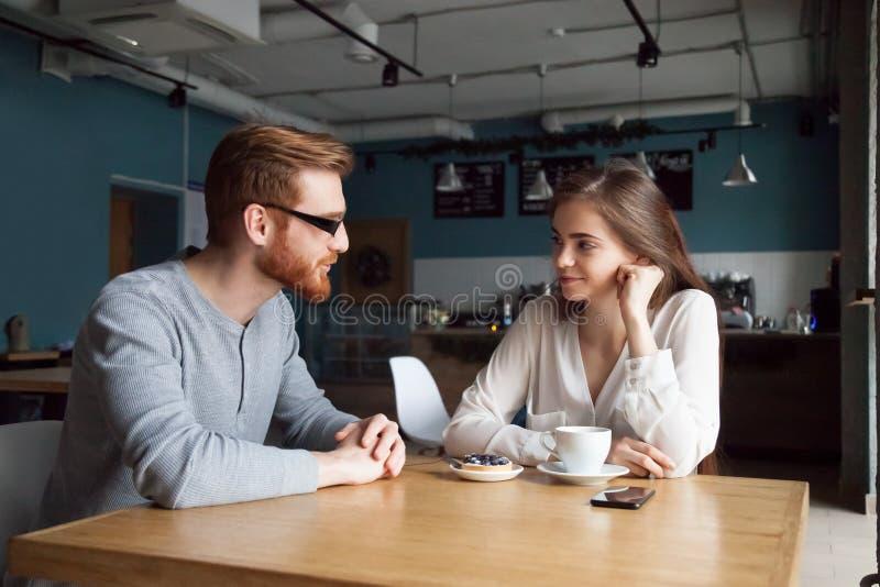 Junger Kerl erhalten mit hübschem Mädchen im Café bekannt gemacht lizenzfreie stockfotos