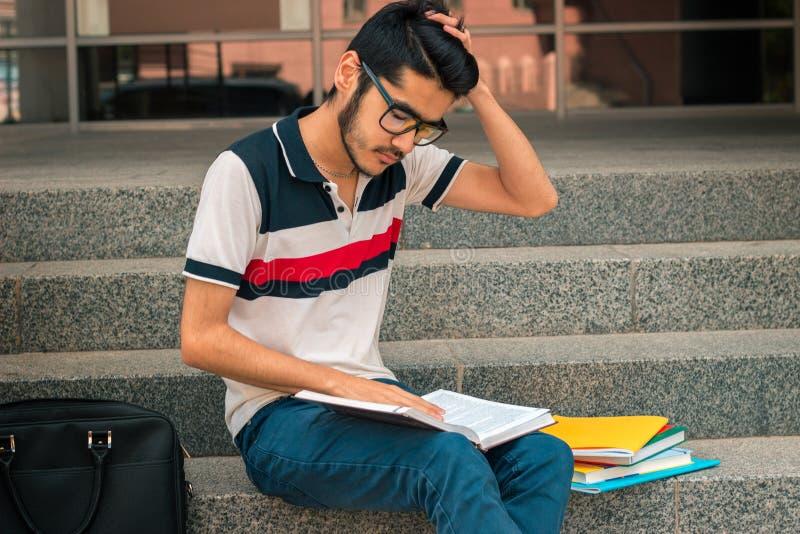 Junger Kerl mit dem schwarzen Haar sitzt auf den Schritten und untersucht das Buch lizenzfreie stockfotografie