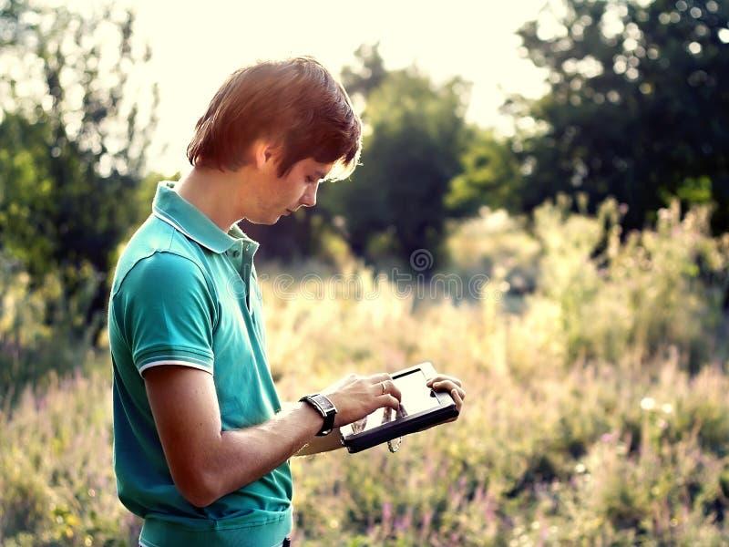 Junger Kerl mit einer Tablette draußen stockfotografie