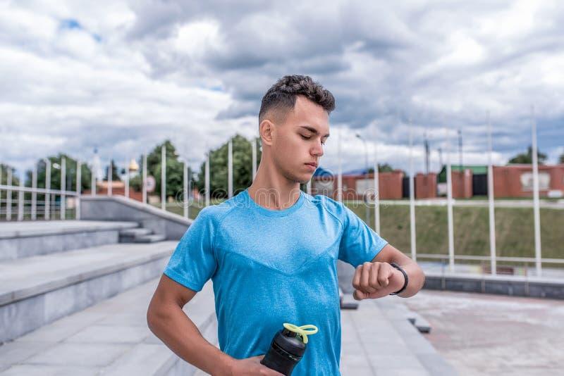 Junger Kerl, Sport Athlet, Sommerstadt, schaut Uhr, überprüft Impulsherzschlag, Stoppuhrzeittimer, Flaschenprotein stockbild