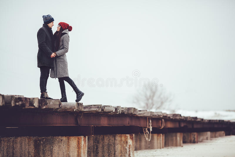 Junger Kerl und Mädchen in der Winterabnutzung, Umarmung und genießen die Landschaft des Winters lizenzfreies stockfoto