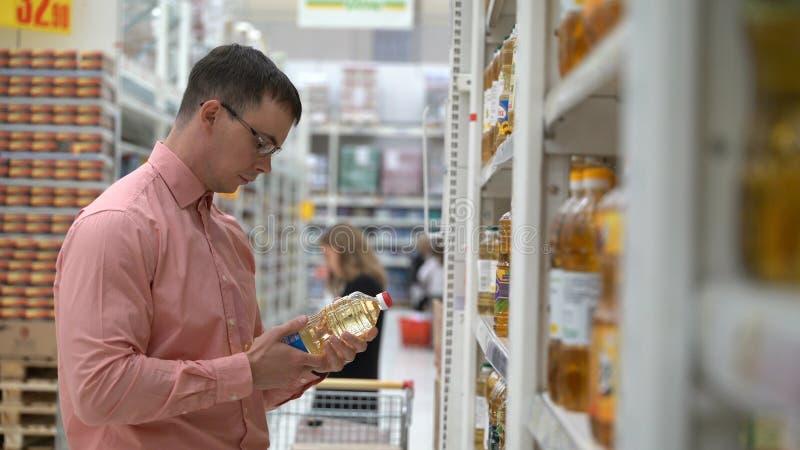Junger Kerl wählt ein Sonnenblumenöl in einem Speicher oder in einem Supermarkt lizenzfreie stockfotos