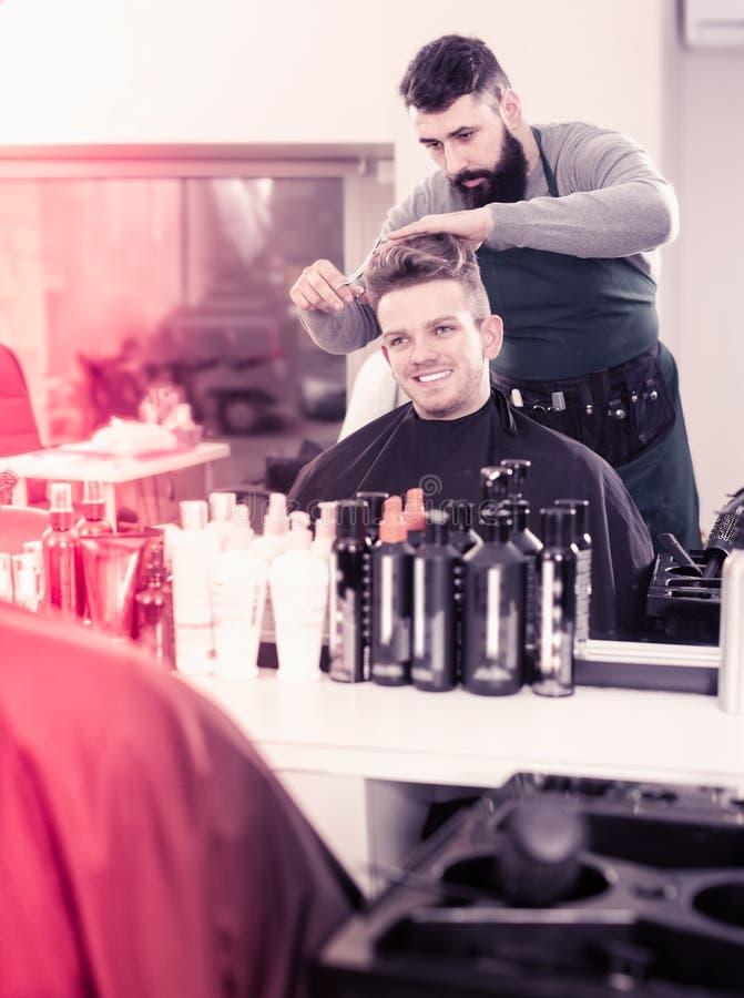 Junger Kerlstilist, der Haarschnitt für glücklichen Mannkunden am haird schafft stockbild
