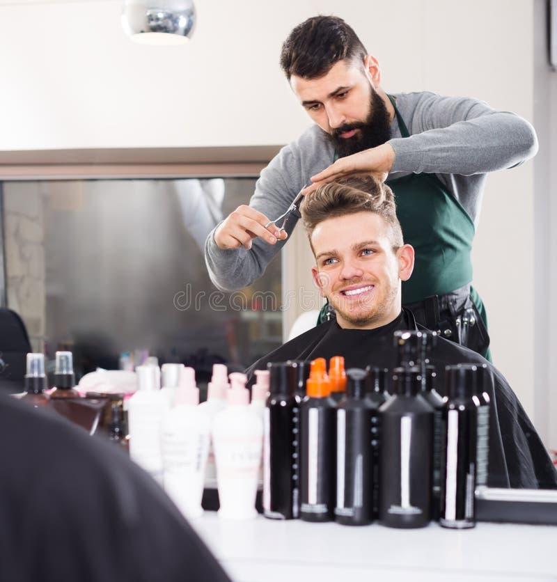 Junger Kerlstilist, der Haarschnitt für lächelnden Mannkunden am hai schafft stockfotos