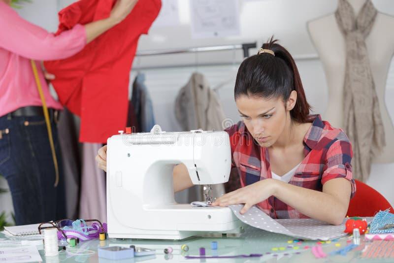 Junger Kleidungsdesigner, der Mustergewebe macht stockfoto
