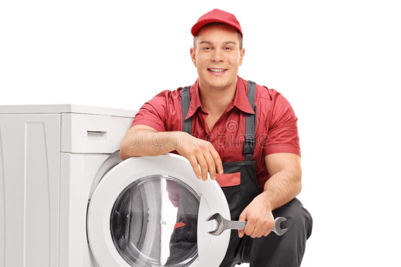 Junger Klempner, der durch eine Waschmaschine aufwirft lizenzfreies stockfoto
