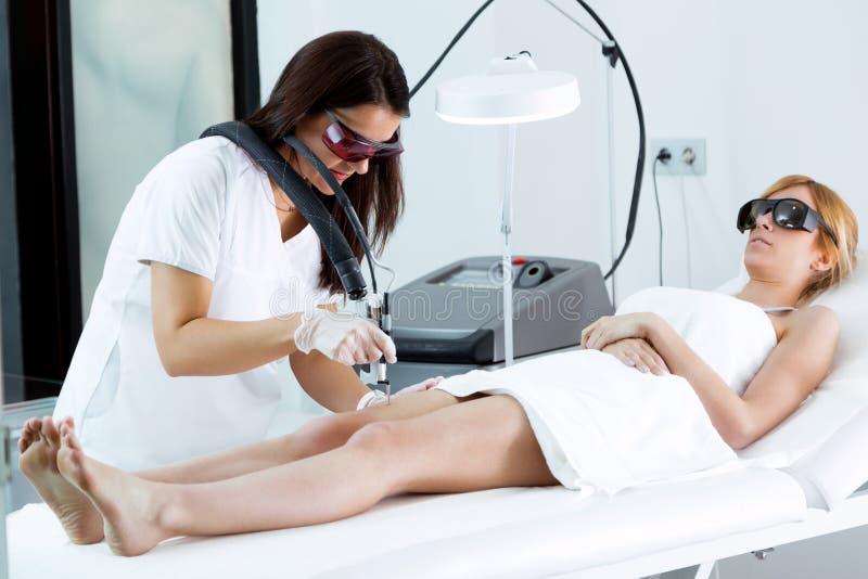 Junger Kosmetiker, der Beinhaar mit einem Laser zu ihrem Kunden im Schönheitssalon entfernt lizenzfreie stockfotos