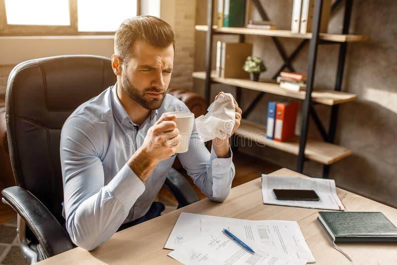 Junger kranker Geschäftsmann sitzen bei Tisch in seinem eigenen Büro Er hält weiße Serviette und Schale in den Händen Kerl ist kr lizenzfreie stockfotos