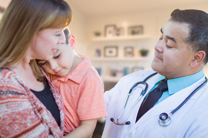 Junger kranker Junge und Mutter, die mit hispanischem Doktor in Offic besucht stockfoto
