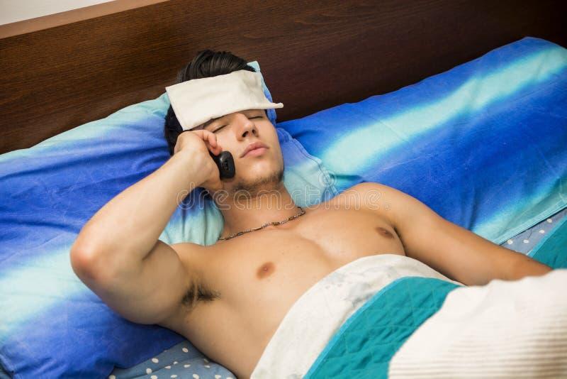 Junger kranker oder unwohler Mann im Bett Doktor anrufend lizenzfreie stockfotos