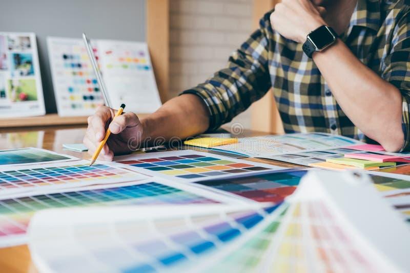 Junger kreativer Grafikdesigner, der Grafiktablette zum choosin verwendet lizenzfreie stockbilder
