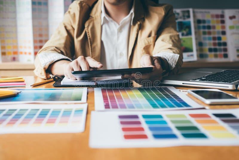 Junger kreativer Grafikdesigner, der Grafiktablette zum choosin verwendet stockbilder