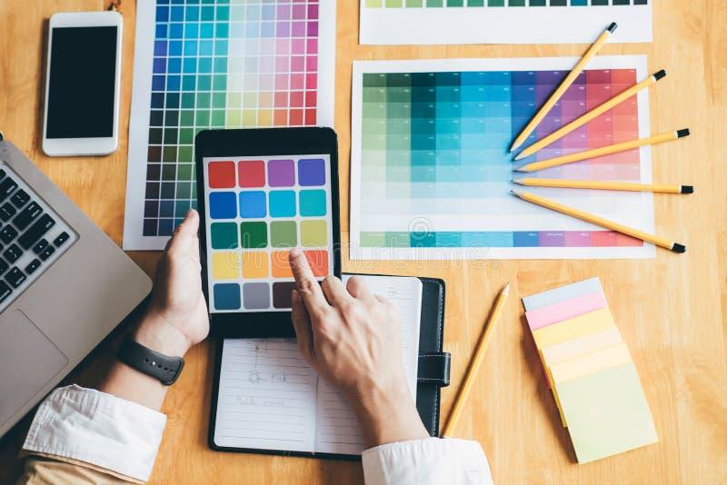 Junger kreativer Grafikdesigner, der Grafiktablette zum choosin verwendet lizenzfreies stockbild