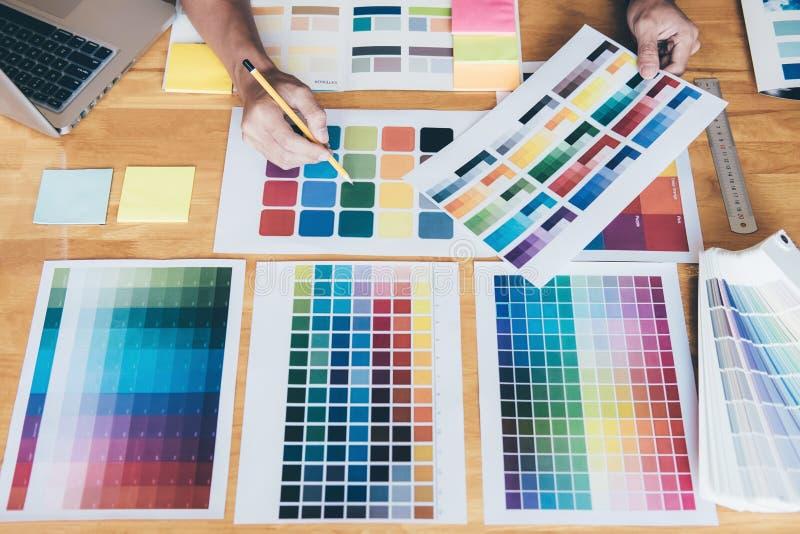 Junger kreativer Grafikdesigner, der Grafiktablette zum choosin verwendet stockfotografie