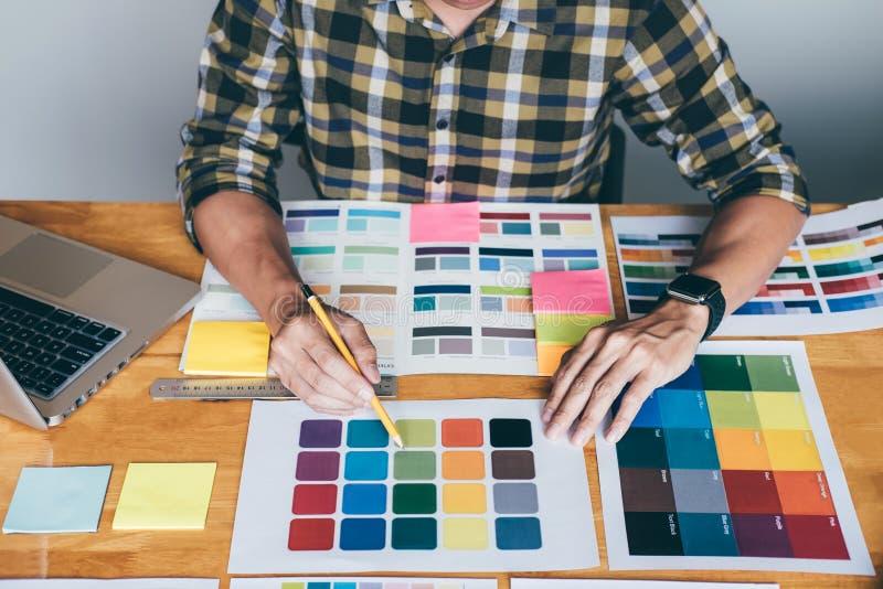 Junger kreativer Grafikdesigner unter Verwendung der Grafiktablette zum Wählen des Farbmusterbeispieldiagramms für Auswahlfarbton stockfotos