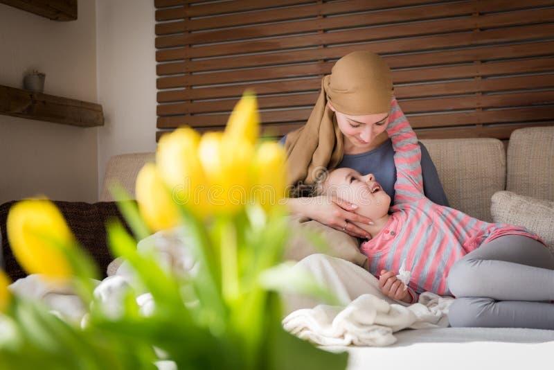 Junger Krebspatient der erwachsenen Frau, der zu Hause Zeit mit ihrer Tochter, entspannend auf der Couch verbringt Krebs und Fami lizenzfreie stockfotografie