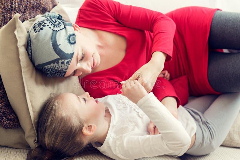 Junger Krebspatient der erwachsenen Frau, der zu Hause Zeit mit ihrer Tochter, entspannend auf Couch verbringt Krebs- und Familie lizenzfreie stockbilder