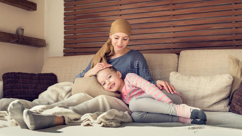 Junger Krebspatient der erwachsenen Frau, der zu Hause Zeit mit ihrer Tochter, entspannend verbringt Krebs- und Familienförderung lizenzfreie stockbilder