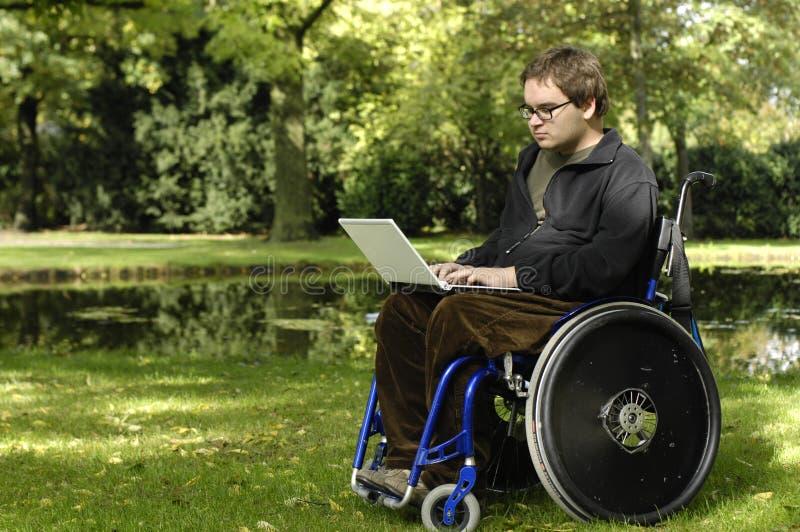 Junger Kursteilnehmer auf einem Rollstuhl am Park lizenzfreie stockbilder