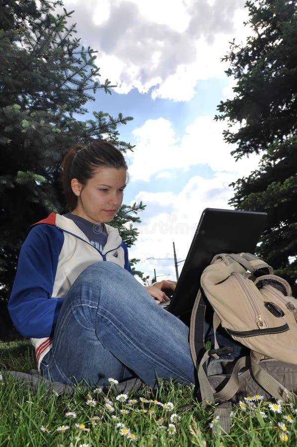 Junger Kursteilnehmer, der draußen mit Laptop erlernt lizenzfreie stockfotos