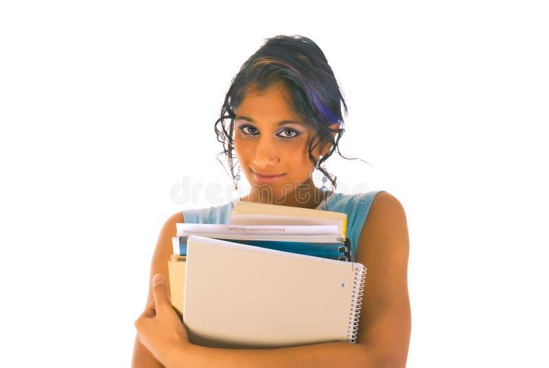 Junger Kursteilnehmer, der mit einem Stapel Büchern steht stockfotos