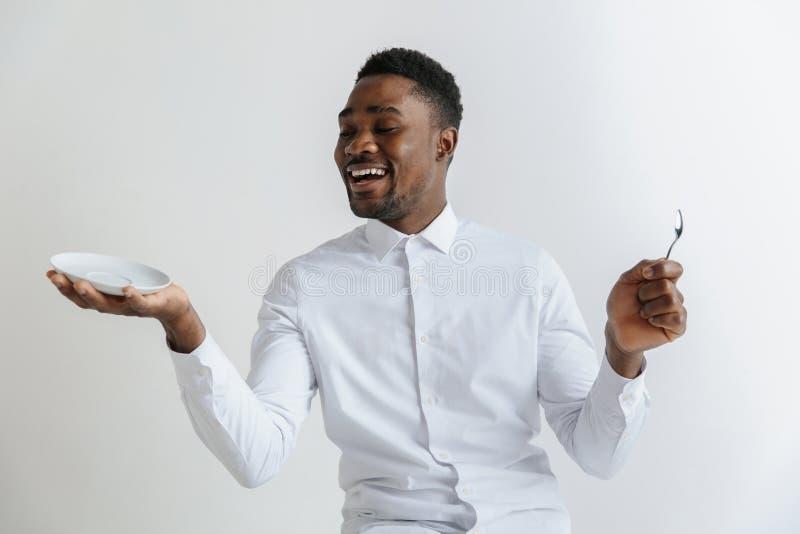 Junger lächelnder attraktiver Afroamerikanerkerl, der leeren Teller halten und Löffel lokalisiert auf grauem Hintergrund lizenzfreie stockfotografie