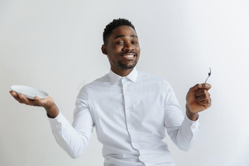 Junger lächelnder attraktiver Afroamerikanerkerl, der leeren Teller halten und Löffel lokalisiert auf grauem Hintergrund lizenzfreies stockfoto