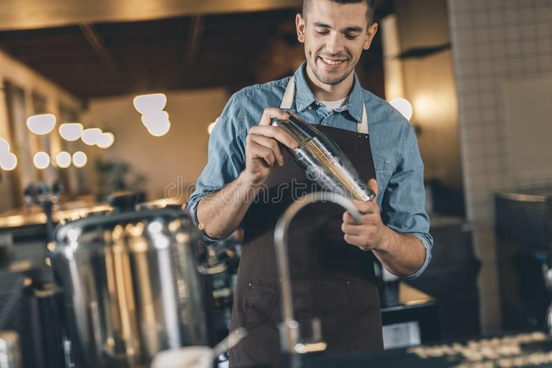 Junger lächelnder Barmixer, der Mixbecher bei der Arbeit verwendet stockfoto