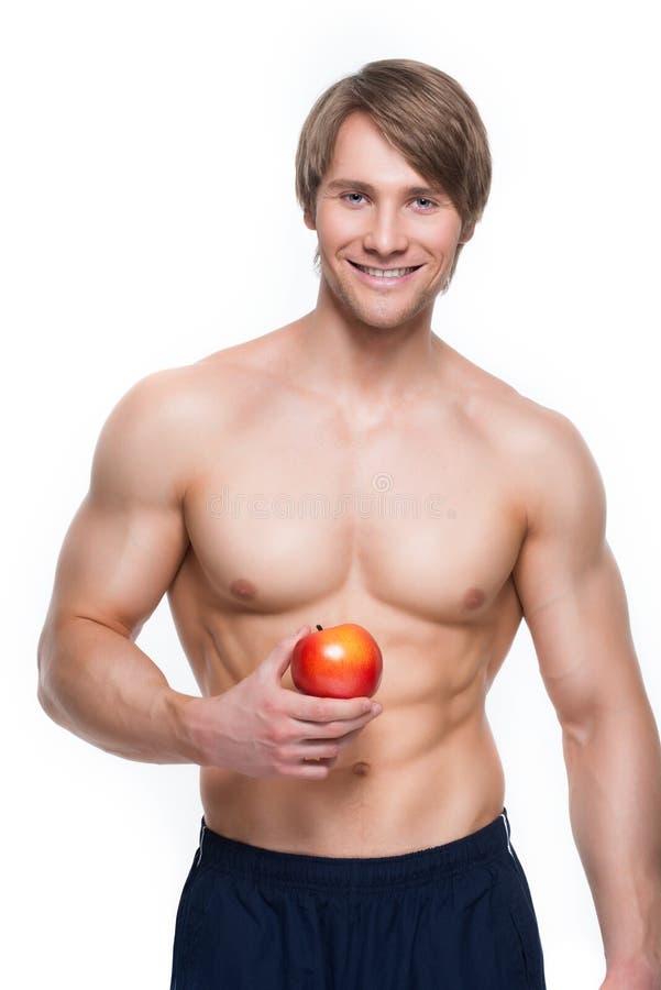 Junger lächelnder Bodybuilder, der Apfel hält stockfotos