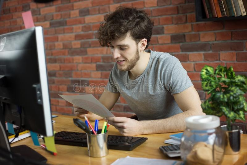 Junger l?chelnder Designer oder K?nstler, die an seinem Arbeitsplatz betrachtet Farbpalette im Dachbodenartb?ro arbeitet stockbild